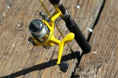 Went Fishing. Yellow fishing reel and pole Stock Photo