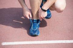 Werden fertig zum Rütteln Hände, die Spitzeturnschuh-Laufbahnhintergrund binden Hände des Sportlers mit Pedometer stockbild