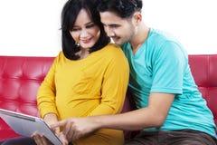 Werdende Mutter mit dem Ehemann, der Tablette verwendet Stockbilder