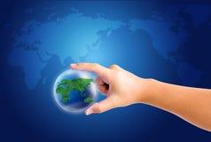 Wereld in hand en globaal op blauwe kaartachtergrond Royalty-vrije Stock Afbeeldingen