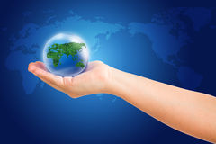 Wereld in hand en globaal op blauwe kaartachtergrond Stock Fotografie
