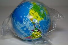 Wereld in plastiek wordt verpakt dat plastic verontreinigingsconcept royalty-vrije stock afbeeldingen
