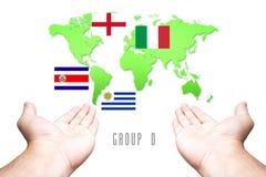 Wereldbeker 2014 Vlag groep-D met Hand en Wereldkaartachtergrond Stock Foto's