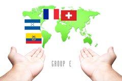 Wereldbeker 2014 Vlag groep-E met Hand en Wereldkaartachtergrond Stock Afbeelding
