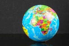 Wereldbol met bezinning over zwarte stock foto