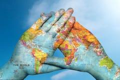 Wereldkaart in handen tegen de hemel royalty-vrije stock foto's