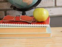 Wereldleraren & x27; Dag in school Stilleven met boeken, bol, Apple, glazen Stock Afbeeldingen
