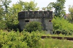 Wereldoorlog II kleine concrete die bunker als kasteel wordt gevormd naast spoorwegsporen wordt en met overwoekerde bomen en word royalty-vrije stock fotografie