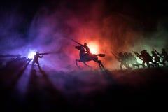 Wereldoorlogambtenaar (of strijders) ruiter op paard met een zwaard klaar te vechten en militairen op een donkere mistige gestemd Stock Foto's