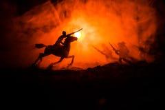 Wereldoorlogambtenaar (of strijders) ruiter op paard met een zwaard klaar te vechten en militairen op een donkere mistige gestemd Stock Foto