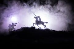 Wereldoorlogambtenaar (of strijders) ruiter op paard met een zwaard klaar te vechten en militairen op een donkere mistige gestemd Stock Fotografie