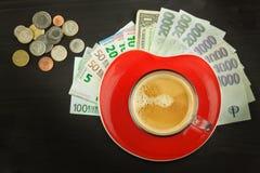 Wereldwijde handelkoffie Kop van Koffie en geld Geldige bankbiljetten op een houten lijst Het probleem van corruptie stock afbeelding