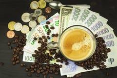 Wereldwijde handelkoffie Kop van Koffie en geld Geldige bankbiljetten op een houten lijst Het probleem van corruptie royalty-vrije stock foto
