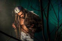 Werewolf με ένα δέρμα στο δέρμα του και μακριά καρφιά μεταξύ του δέντρου branc Στοκ Εικόνες