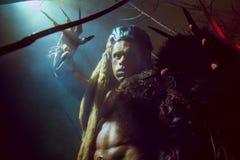 Werewolf με τα μακριά καρφιά και τα στριμμένα δόντια μεταξύ των κλάδων Στοκ Εικόνες