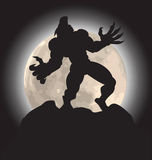 Werewolf howl silhouette. Werewolf silhouette howling on mountain peak with a full moon behind Royalty Free Stock Image