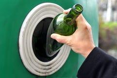 Werfen Sie eine Glasflasche in eine Glaswertstofftonne stockfotografie