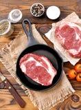 Werfen Sie Eisenstein mit rohem ribeye Steak auf hölzernem Hintergrund Lizenzfreie Stockfotos