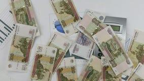 Werfen Sie Rubel auf dem Diagramm mit Taschenrechner und Stift Werfendes Geld verlegen unten stock footage