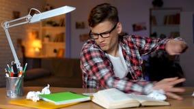 Werfende B?cher des aggressiven Studenten der Tabelle, k?nnen Aufgabe, schwere Aufgabe nicht l?sen lizenzfreie stockfotos