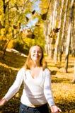 Werfende Blätter des glücklichen Mädchens lizenzfreie stockfotos