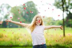 Werfende Blumenblätter des jungen Mädchens stockbilder