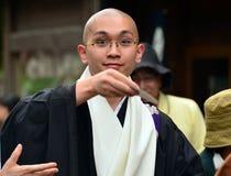 Werfende Glücksbringer des jungen buddhistischen Priesters zum croud Stockbilder
