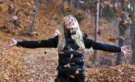 Werfende Herbstblätter des jungen Mädchens Lizenzfreies Stockfoto