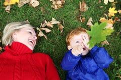 Werfende Herbstblätter des Kindes Lizenzfreie Stockfotos