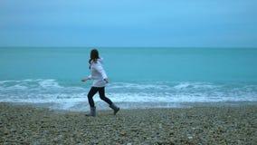 Werfende Kiesel der jungen Frau in Ozean, schäumende Wellen, die an Land in LangsammO spritzen stock video footage