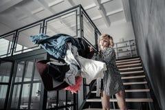 Werfende Kleidung der Frau des Ehemanns weg von ihrer Wohnung stockbild