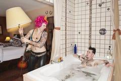 Werfende Lampe der rosa behaarten Frau auf Mann in der Badewanne Lizenzfreie Stockfotos