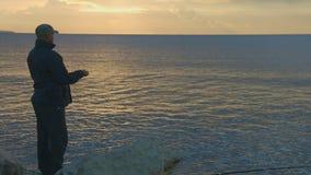 Werfende Steine des Fischers in Wasser bei Sonnenaufgang, Sonnenuntergang Magische Stunde, Entspannung stock footage