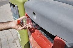 Werfender Abfall in Abfalleimer, Hand wirft Flasche in containe Stockbilder