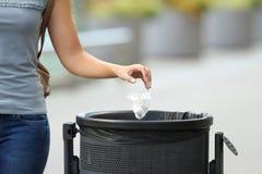 Werfender Abfall der bürgerlichen Frau in einem Abfalleimer Lizenzfreie Stockfotos