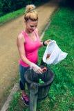 Werfender Abfall der Frau nachdem dem Plogging Stockfotografie