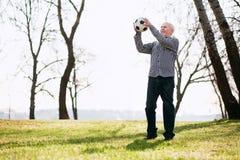 Werfender Ball des anziehenden reifen Mannes lizenzfreies stockfoto