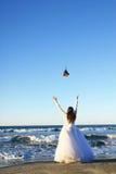 Werfender Blumenstrauß der Braut im Meer Lizenzfreie Stockfotografie