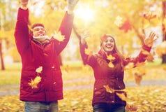 Werfender Herbstlaub der glücklichen jungen Paare im Park lizenzfreies stockbild