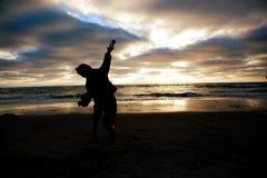 Werfender Sand des kleinen Jungen am Strand Stockfoto