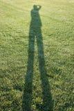 Werfender Schatten der Person auf Gras Lizenzfreie Stockbilder