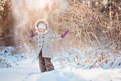 Werfender Schnee des glücklichen Kindermädchens im sonnigen Wald des Winters Stockbild