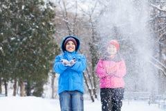 Werfender Schnee des Jungen und des Mädchens in Luft Stockfotografie