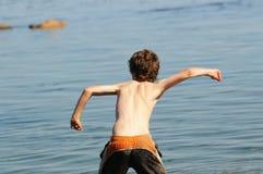 Werfender Stein des Jungen im Meer Stockbild