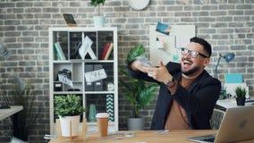 Werfendes Geld des aufgeregten Kerls, das Reichtum im Büro allein genießend lacht stock video footage