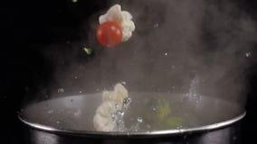 Werfendes Gemüse in gekochtes Wasser stock footage