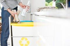 Werfendes Papier der Hausfrau in Behälter lizenzfreie stockfotografie