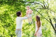 Werfendes Sohnhoch des Vaters beim Spielen Lizenzfreie Stockfotos
