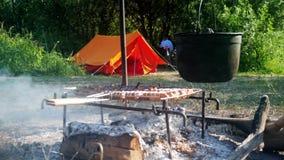 Werferlager, das auf einer kampierenden Szene des Feuers kocht, die ein Topf mit dem Lebensmittel, das vorbereitet wird, über das stock video footage