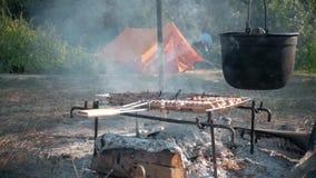 Werferlager, das auf einer kampierenden Szene des Feuers kocht, die ein Topf mit dem Lebensmittel, das vorbereitet wird, über das stock video